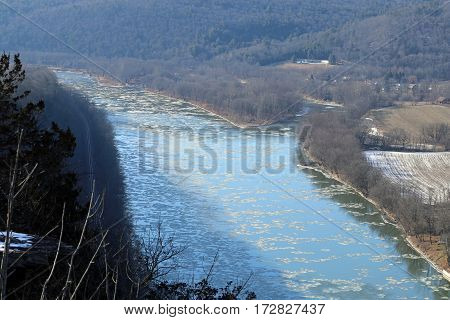 Ice floating down the Susquehanna River with railroad tracks going around the bend.