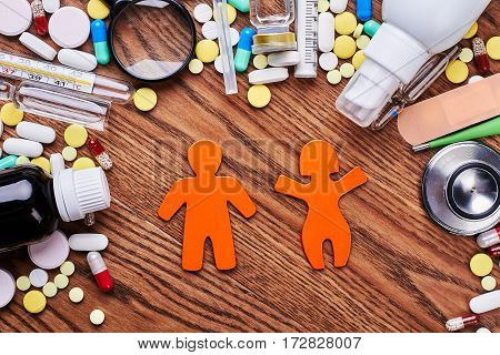 Pills, stickmen on wooden backdrop. Medical center protects your health.