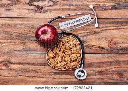 Red apple, walnuts and stethoscope. Congratulatory message to a doctor.