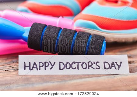 Skipping rope, gumshoes and card. Happy Doctor's day message.