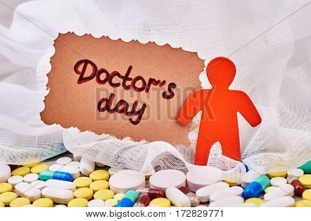 Stickman and scattered pills. Doctor's Day card for surgeon.