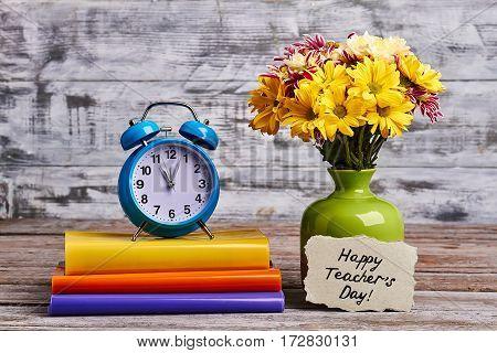 Chrysanthemums, alarm clock and card. Creative present for teacher.