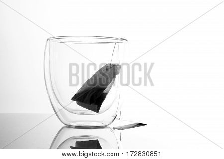 tea bag and transparent glass / Tea is an aromatic beverage commonly prepared by pouring hot or boiling water over cured leaves
