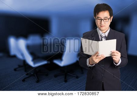 Confident Asian Businessman Reading Notebook Or Document File In Meeting Room.