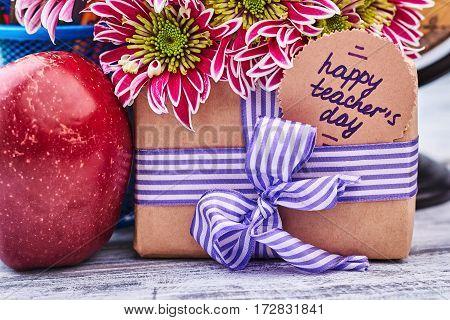 Gift box, apple and flowers. Teacher, I love you.