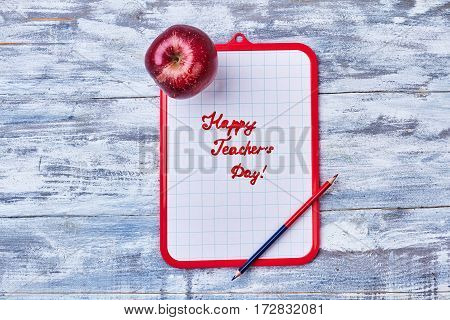 Clipboard, pencil and apple. Brief congratulation to Teacher's Day.