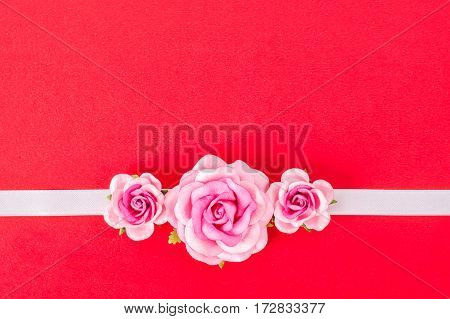 Roses and white ribbon on red background with copyspace for your text or message.