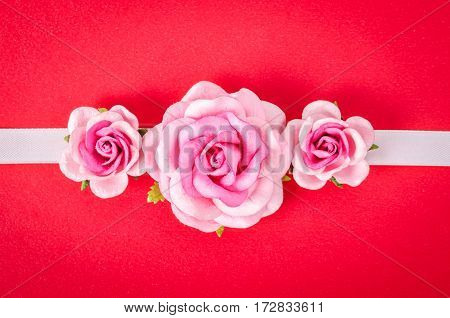 The pink roses on red paper background.
