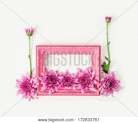 Pink vintage photo frame with chrysanthemum flower on white background.