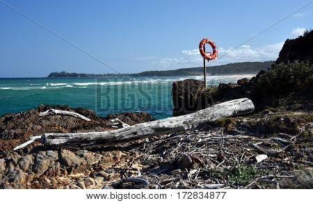 Dry wood debris and an orange life buoy at Tuross Head.