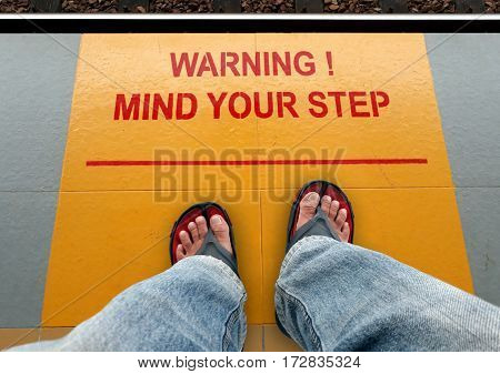 Mind your step signage on a train platform with a man standing