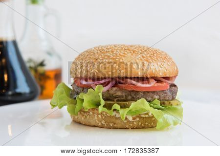 Tasty classical burger with meat cheese lettuce onion, tomato and sauce on white table
