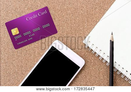 mobile phone notebook and credit card on a brown wooden table