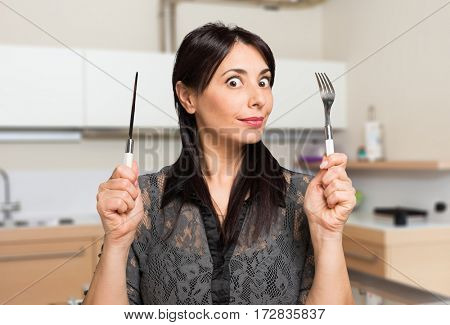 Hungry woman holding fork and knife in her kitchen