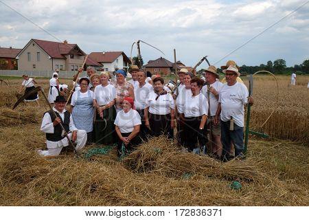 TRNOVEC, CROATIA - JULY 09, 2016: Farmers posing in the field during harvest in Trnovec, Croatia on July 09, 2016.