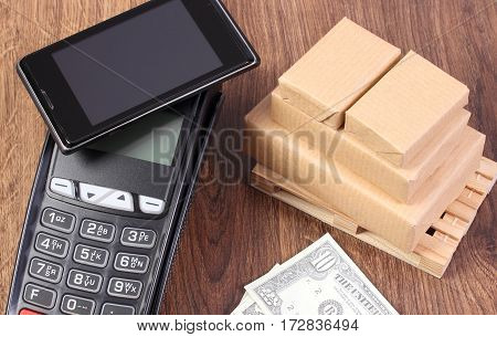 Payment Terminal With Mobile Phone With Nfc Technology, Currencies Dollar And Wrapped Boxes On Woode