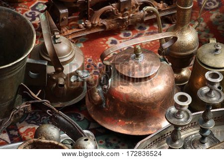 On an old carpet there are different old metal things. In the centre there is a copper teapot.