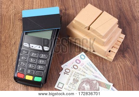 Payment Terminal With Credit Card, Polish Currency Money And Wrapped Boxes On Wooden Pallet