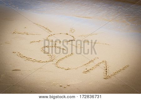 Word sun and shape of sun written on sand at the beach by the sea summer and vacation time