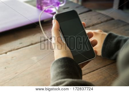 Woman hand on smart phone on wooden table stock photo