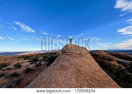 Man in successful pose on mountain top. Devil's Garden trail. Arches National Park. Moab. Utah. United States.