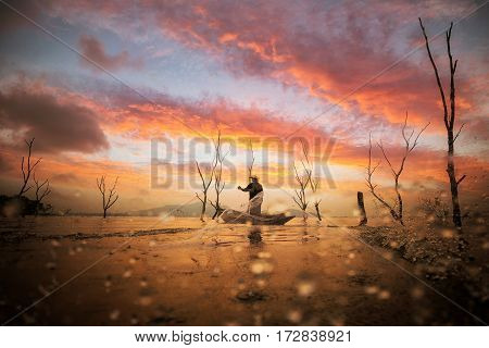 Fisherman working with net on the boat and sunset background Thailand. People nature job asia and job concept
