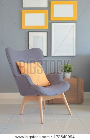 Retry Style Armchair With Orange Pillow In Living Room With Wall Of Picture Frame In Background