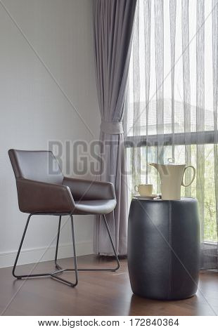 Dark Brown Chair At The Corner With Ceramic Coffee Set On The Table