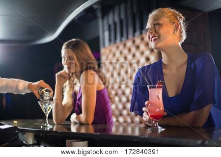 Waiter pouring a cocktail in woman glass at bar counter in bar