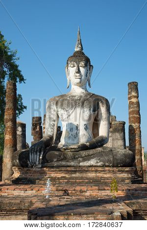 Ancient sculpture of a sitting Buddha close up. Ruins of the Buddhist temple Wat Mahathat. Sukhothai. Thailand