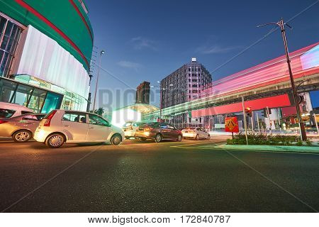Cars and monorail rush through the Bukit Bintang intersection at night in Kuala Lumpur Malaysia capital city.