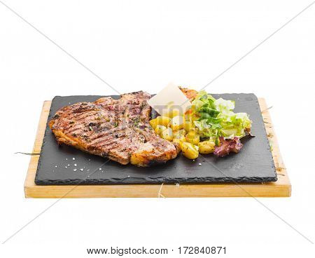 Cooked big steak on board with potatoes and greens