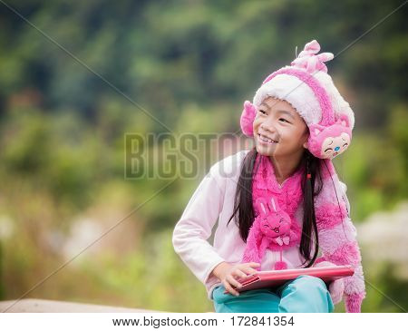 Funny little Asian girl learning with tablet pc in the park