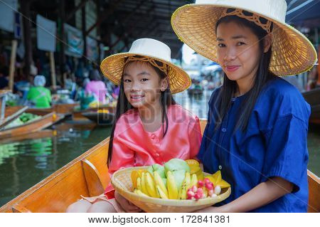 Chikd and mother sit on the boat and hold the fruit basket in Traditional floating market bangkok Thailand.
