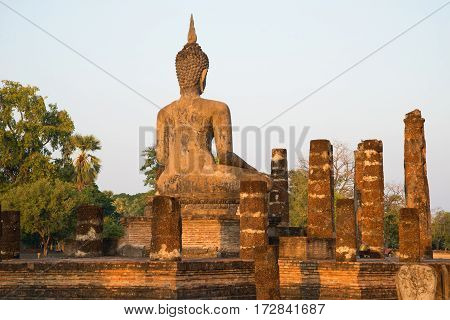Ancient sculpture of a seated Buddha on the ruins of the temple Wat Chana Songkhram. The view from the back. Sukhothai, Thailand