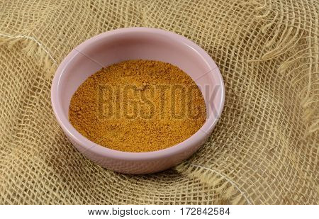 Ground mace spice in pink condiment dish on burlap