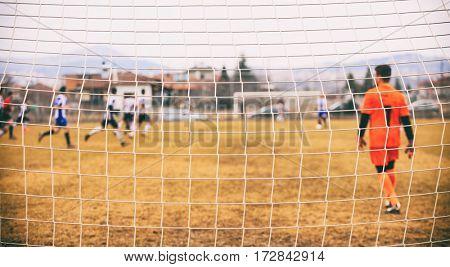 Goalkeeper behind a football goal net