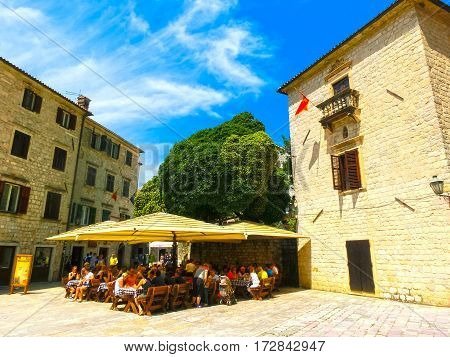 Kotor, Montenegro - May 07, 2014: People sittiing at cafe on St. Luke's square surrounded by traditional stone houses at Kotor's Old Town, Montenegro on May 07, 2014. People walking