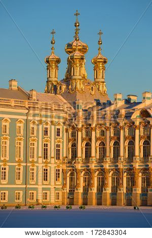 Domes of Church of the Resurrection in beams of the sunset sun. A fragment of Catherine Palace in Tsarskoye Selo, Russia