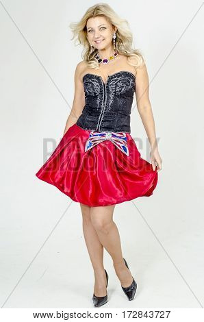 Beautiful blonde woman artist in chermnm corset with sequins and red skirt with belt bow