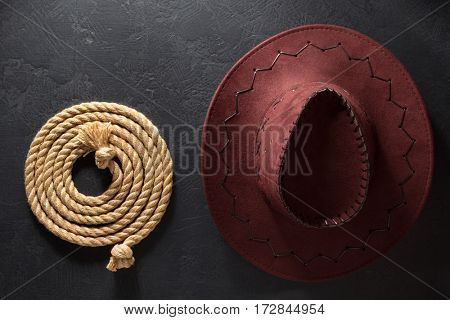 cowboy hat and lasso on black background texture
