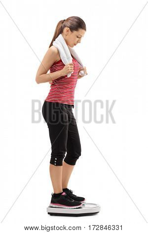 Full length profile shot of a woman with a towel standing on a weight scale isolated on white background