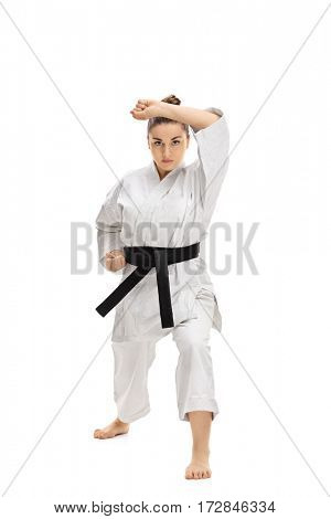 Full length portrait of a girl wearing a kimono doing a karate kata isolated on white background