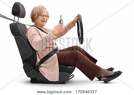 Joyful elderly woman holding a car key and sitting in a car seat isolated on white background