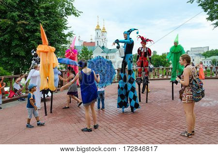 VITEBSK BELARUS - JULY 13 2016: Buffoons on stilts near puppet theater during festival Slavic Bazaar Vitebsk Belarus