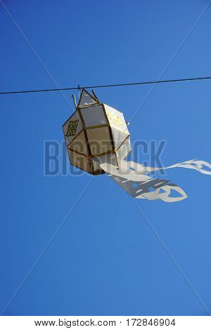 white and gold local hand craft lantern with blue sky background