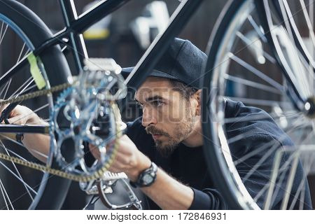 Close-up of professionl constructor of bicycles looking at chain