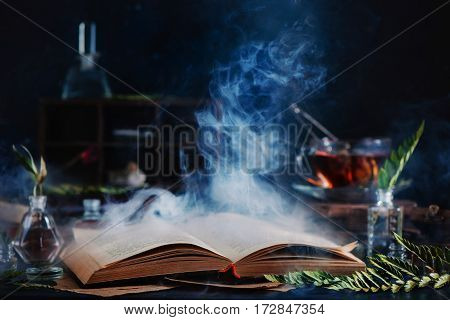 Still life with open spell book, magical smoke, herbs, witchcraft tools and tea