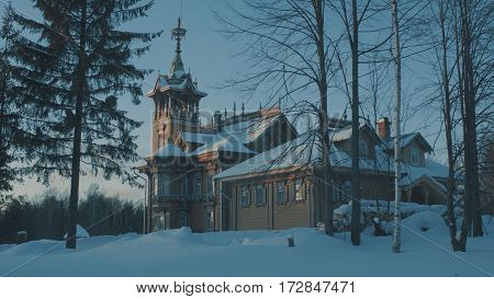 Beautiful traditional snow-covered russian cottage - terem surrounded by a forest and evergreen fir tree near it.