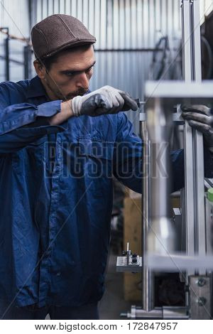 Bearded man in cap and uniform working with screwdriver